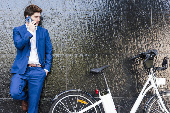 Serious male executive in formal suit leaning on wall while speaking internet on cellphone and standing with hand in pocket near electric bicycle