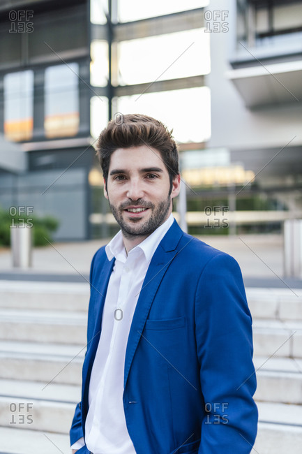 Young smiling bearded businessman in elegant apparel with modern haircut looking at camera near building with staircase in town