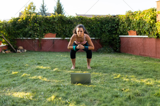 Fit female athlete in sportswear using laptop and doing squats while following online tutorial during training in backyard at sunset