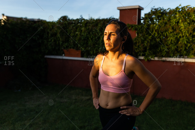 Fit female athlete in sportswear using laptop and doing lunges while following online tutorial during training in backyard at sunset