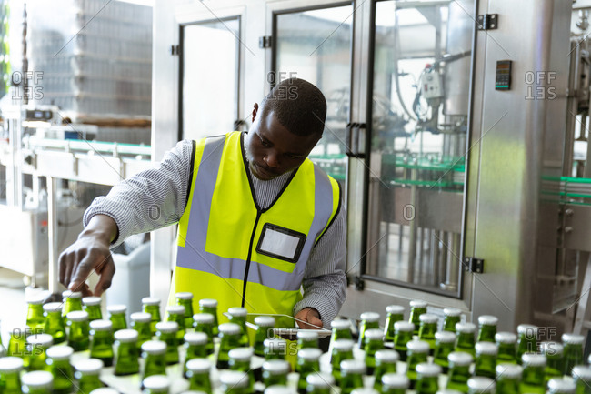 African American man worker working in a brewery, inspecting the bottles at the factory.