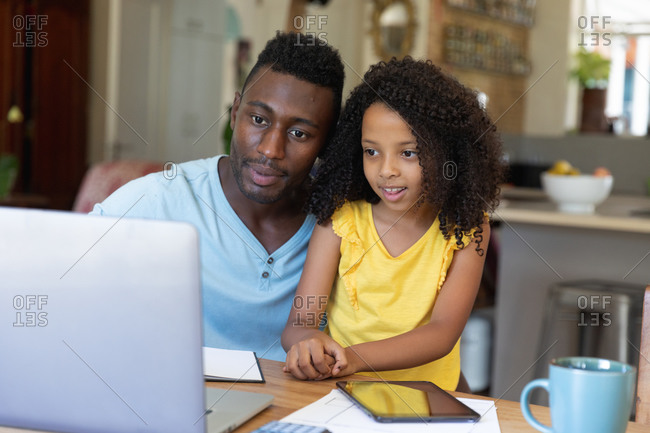 African American father and daughter using a laptop at home, staying at home during lockdown.