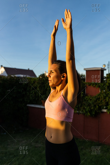 Focused female in sportswear breathing deeply with raised arms while warming up before workout in backyard and looking away