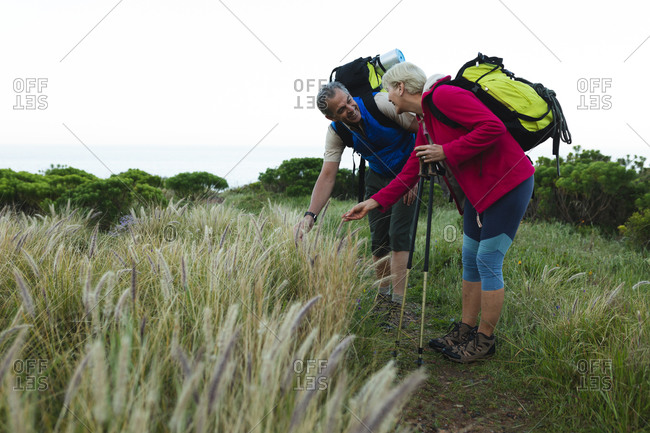 Senior couple spending time in nature together, walking in mountains, touching grass and smiling.