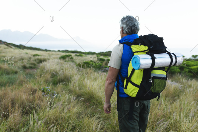 Senior man spending time in nature together, walking in mountains, looking around.