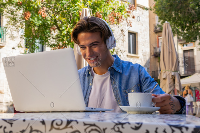 Overjoyed young male in wireless headphones getting incredible news on laptop