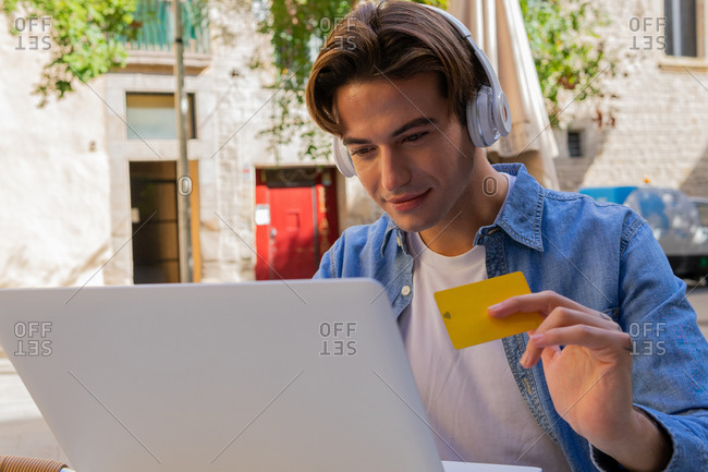 Young content male buyer in headphones with debit card watching netbook while shopping online on street