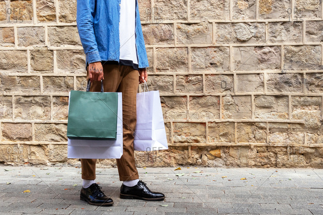 Crop unrecognizable man in trendy apparel with eco friendly bag standing on pavement near rough wall