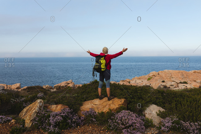 Senior woman spending time in nature, walking in the mountains, enjoying her view, spreading her arms.