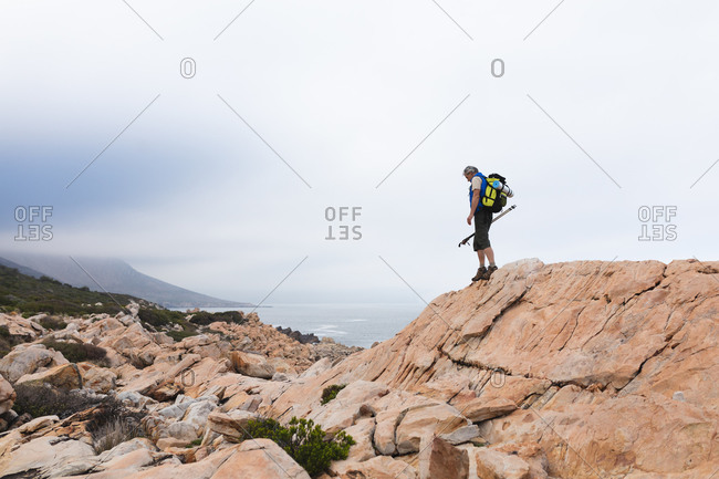 Senior man spending time in nature, walking in the mountains, walking by a cliff.