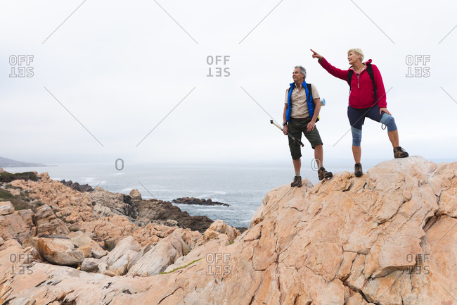 Senior couple spending time in nature together, walking in the mountains, woman is pointing up.