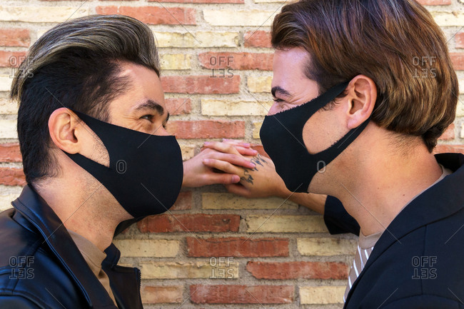 Crop anonymous homosexual friends in stylish wear and face masks looking at each other near wall on street during covid 19 pandemic