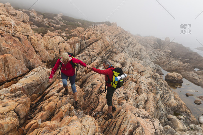Senior couple spending time in nature together, walking in the mountains, holding hands.