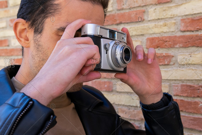 Crop unrecognizable man in trendy wear taking photo on vintage photo camera near shabby wall on street