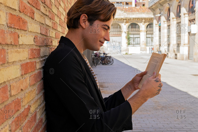 Side view of crop stylish young glad male reading textbook near rough brick wall in town