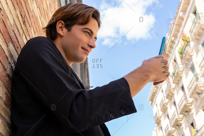 From below side view of young content stylish tattooed male text messaging on cellphone under blue cloudy sky