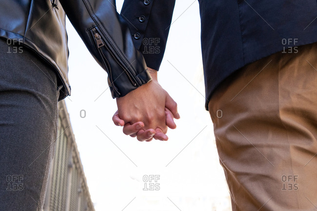From below crop unrecognizable excited gays in trendy apparel holding hands