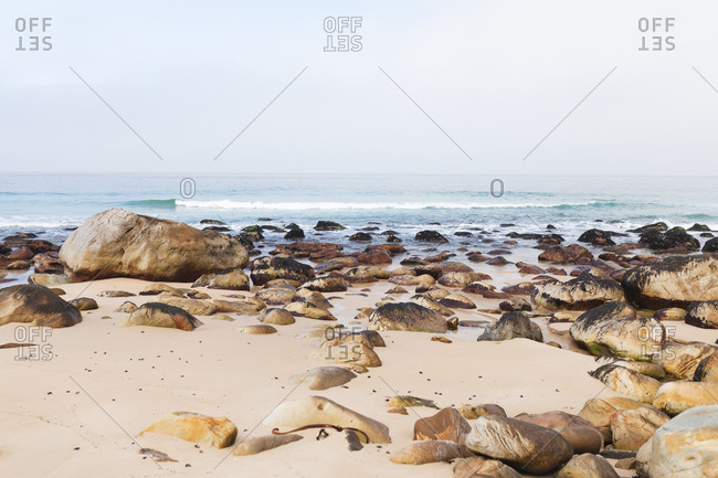 Magnificent view of a calm sea and a beach with yellow sand and quite big rocks lying on the beach.