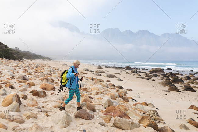 Senior woman spending time in nature, walking in the mountains, walking on the beach.