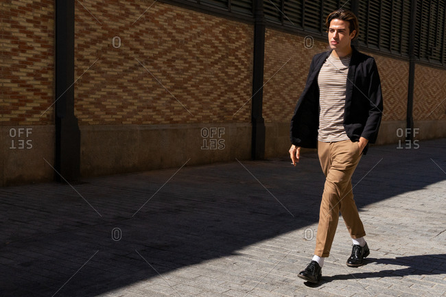 Full body of young trendy male with hand in pocket strolling on tiled pavement near ornamental wall while looking forward in sunlight