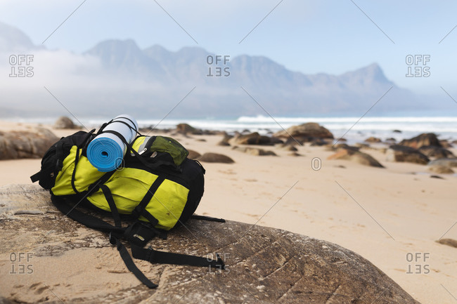 Image of a backpack lying on a rock on a beach by a calm sea.