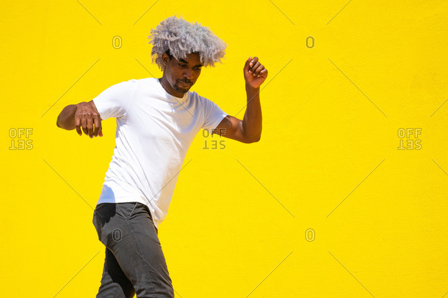 Black dancer dancing on a yellow background. dance and music concept. black man dancing.