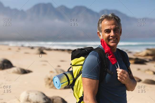Portrait of a senior man spending time in nature, walking on the beach, taking a face mask of, looking at the camera and smiling.