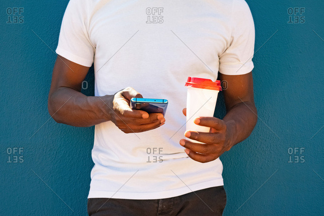 Close up of a black man using the phone and with a coffee to go. takeaway coffee and technology concept.