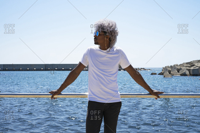 Black man with afro hair relaxing in front of the beach and the sea. beachfront relaxation concept.