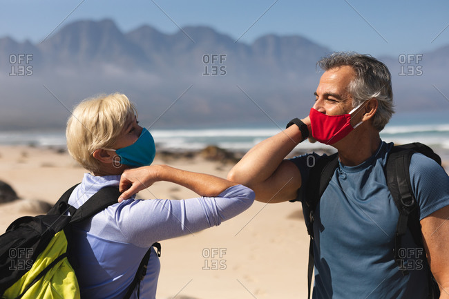 Senior couple spending time in nature together, walking on the beach, wearing face masks and greeting each other with elbows.