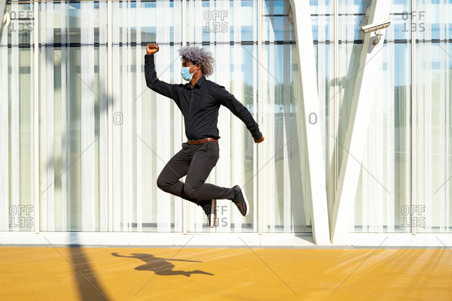 Afro and black businessman with a mask jumping in front of a building. concept of black man with mask. covid-19. social distancing.