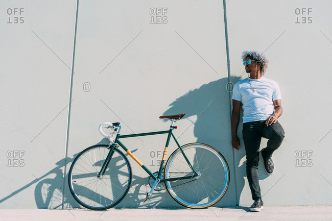 Black cyclist leaning against a gray wall next to his city bike. black rider concept. afro cyclist.
