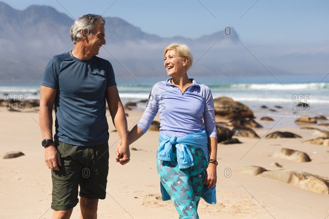 Senior couple spending time in nature together, walking on the beach, holding hands and smiling.