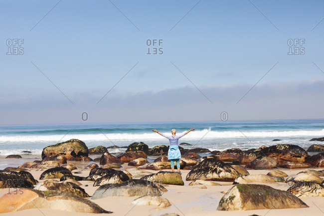 Senior woman spending time in nature, walking on the beach, enjoying the view, raising her arms.