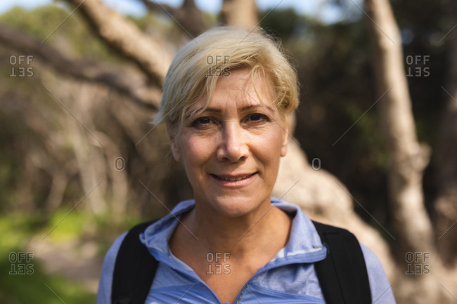 Portrait of a senior woman spending time in nature, walking in the mountains, looking at the camera and smiling.