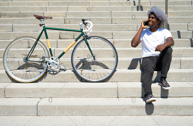 Black man talking on the phone next to his bike. man sitting on the stairs and calling with his cell phone.