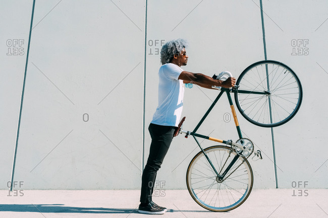 Black and afro man taking the bike and carrying it on a gray background. black cyclist concept.
