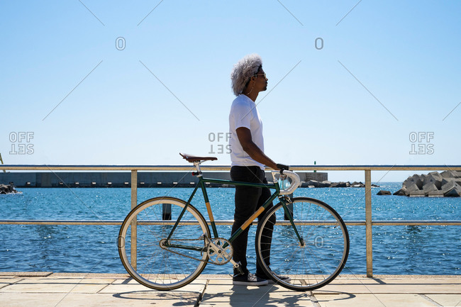 Black man with afro hair carrying a city bike. biker riding with his bike next to him.