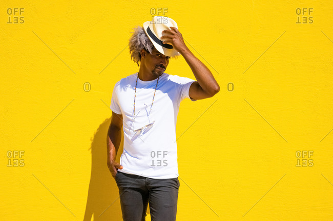 Black man with afro hair putting on a straw hat on a yellow background. hat concept.