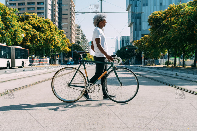 Black and afro man carrying and transporting his city bike in the city. concept of cycling in the city. city bike.