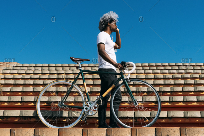 Afro and black man carrying the bike on some stairs. black rider concept. cycling in the city.