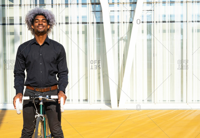 Afro and black businessman taking the bike and smiling. businessman with bicycle. cycle through the city.