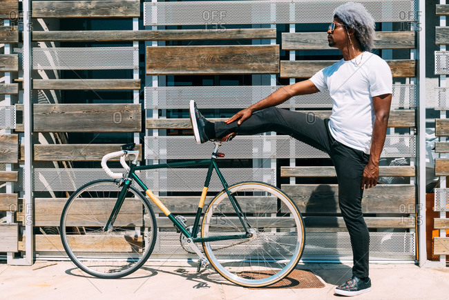 Black biker with afro hair stretching his leg on top of his city bike. black cyclist concept. city bike.