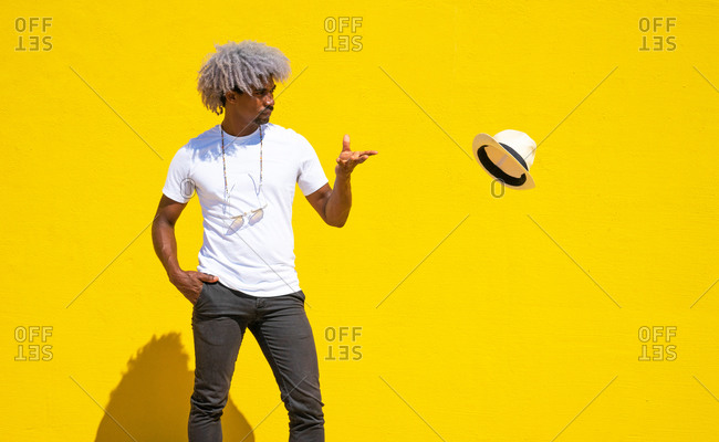 Black man with afro hair throwing a straw hat on a yellow background. concept of throwing a hat.