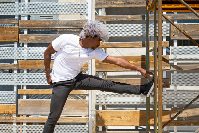 Black man with afro hair athlete jogging stretching his leg. concept of stretching.