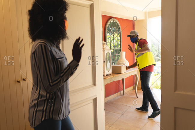 Delivery man wearing face mask delivering package to woman wearing face mask at home.