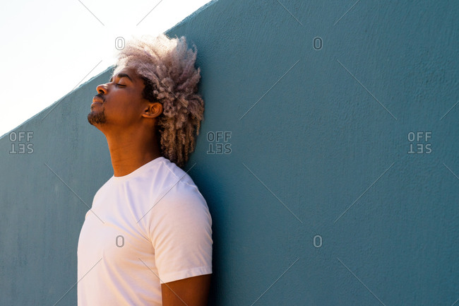 Black man with afro hair dressed in white leaning against a blue wall. afro hair concept. black man in white t-shirt.