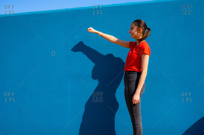 Woman dressed in red raising her fist on a blue background. women's rights. feminism and gender equality. heroine woman.