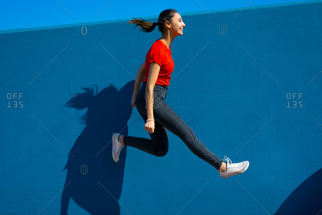 Happy woman in red dress jumping on a blue background. woman jumping and having fun. happiness and joy concept.