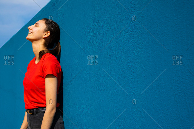 Young woman dressed in red leaning against a blue wall. woman sunbathing and relaxing. blue background.